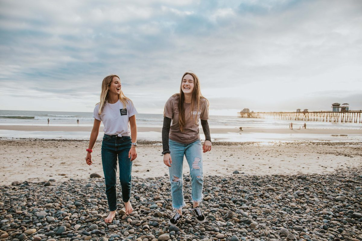 Two women walk barefoot on a beach smiling