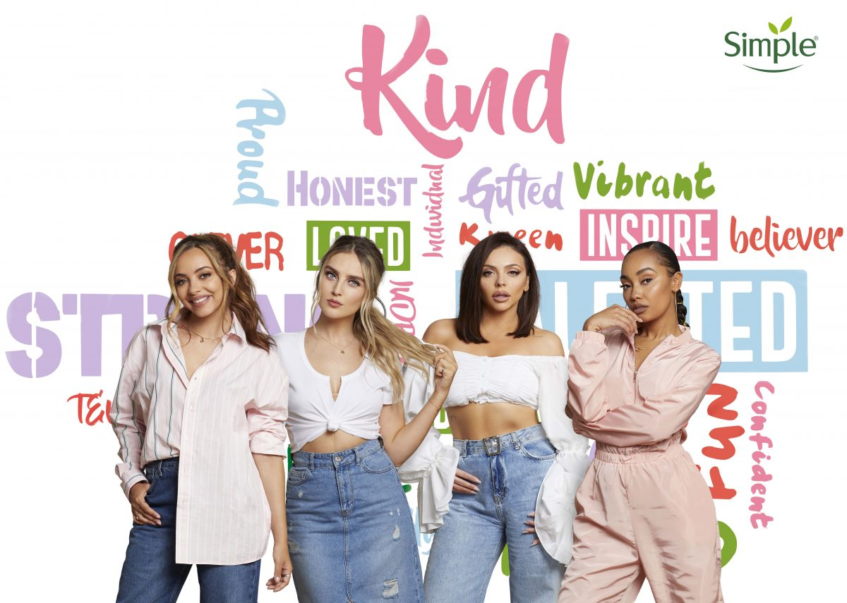 Little Mix in front of a wall of kind words