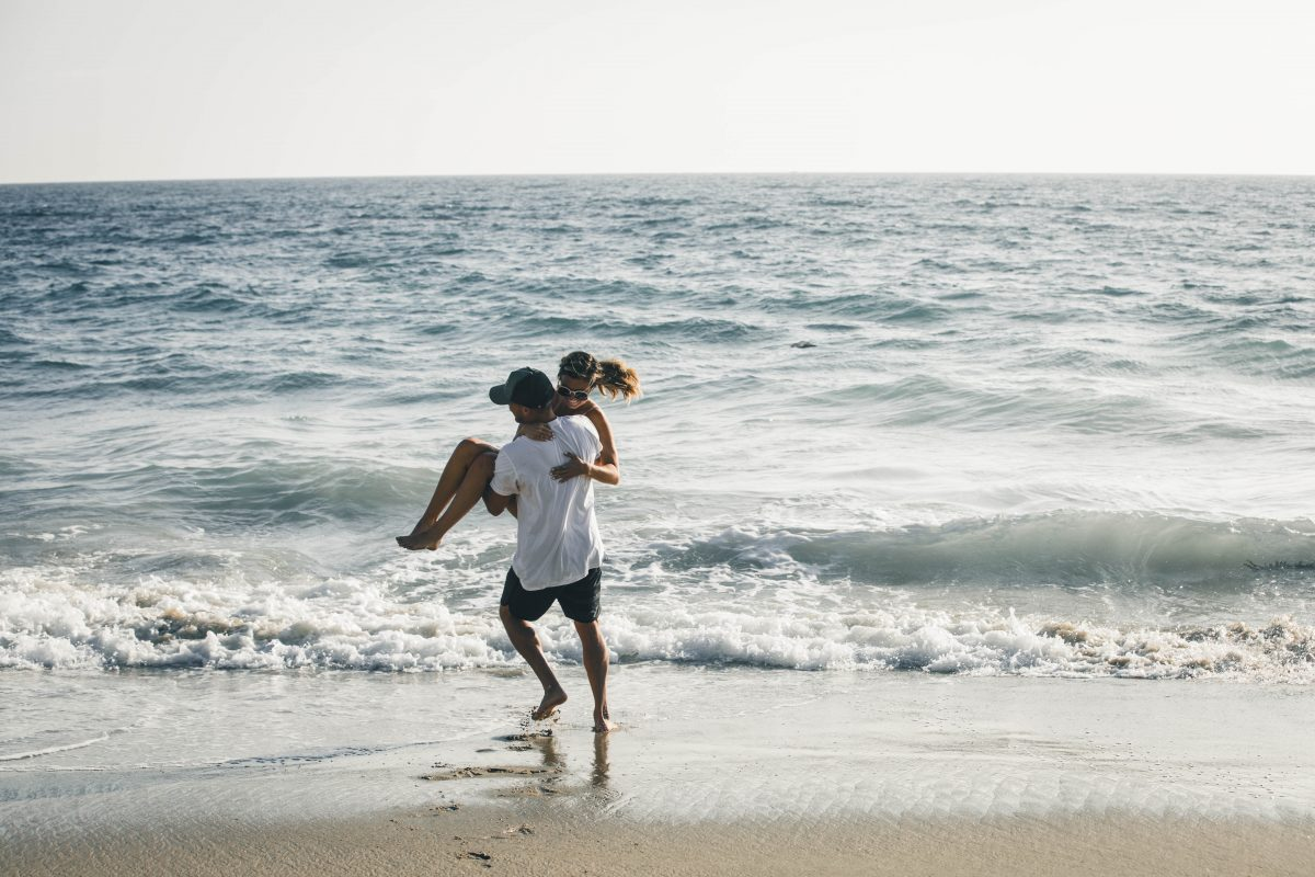 Man carries woman to the sea on the beach