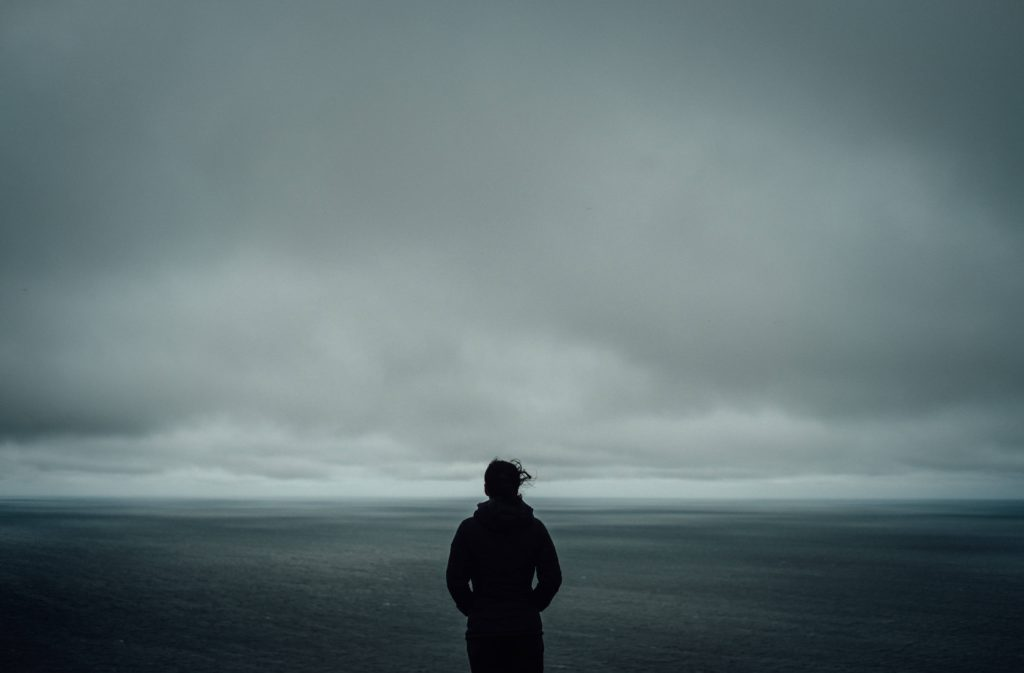 dark skies, clouds, silhouette of a person looking over the sea